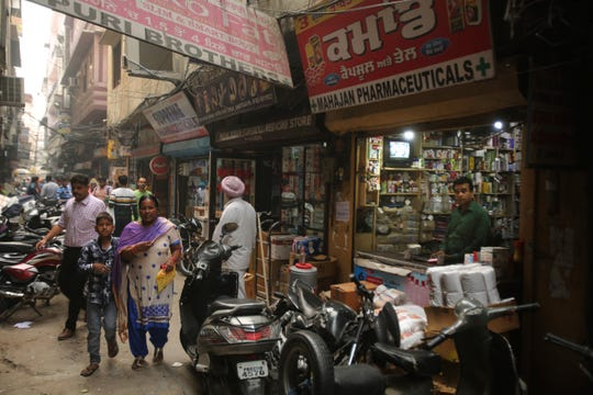 In this Oct. 30, 2019, photo, people walk past drugstores where tramadol was once easily accessible in Amritsar, in the northern Indian state of Punjab.