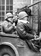 In this Jan. 15, 1945 file photo, U.S. Brig. Gen. Anthony C. McAuliffe, left, and Lt. Gen. George S. Patton, Jr., right, are seated in Jeep after made an inspection tour of the 101st Airborne division.
