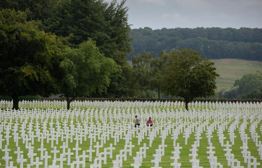 Visitors walk among the headstones at the Henri Chapelle World War II cemetery in Henri Chapelle, Belgium. The cemetery contains 7,992 American war dead and covers 57 acres.