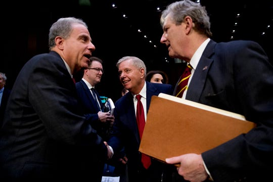 Department of Justice Inspector General Michael Horowitz, left, speaks with Chairman Lindsey Graham, R-S.C., center, and Sen. John Kennedy, R-La., right, after testifying at a Senate Judiciary Committee hearing on the Inspector General's report on alleged abuses of the Foreign Intelligence Surveillance Act, Wednesday, Dec. 11, 2019, on Capitol Hill in Washington.