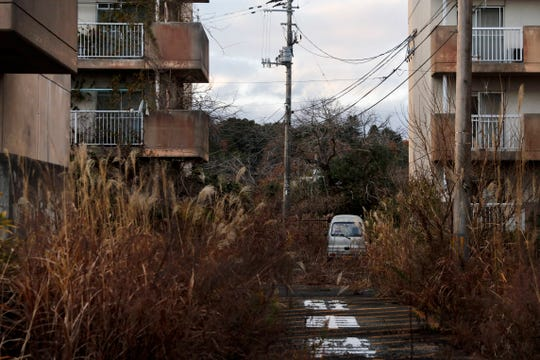 Weeds grow in an abandoned apartment complex Tuesday, Dec. 3, 2019, in Futaba, Fukushima prefecture, Japan.