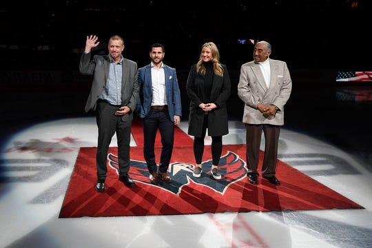 The 2019 U.S. Hockey Hall of Fame class, from left to right, Tim Thomas, Brian Gionta, Krissy Wendell and Neal Henderson stand on the ice before a ceremonial puck drop ahead of an NHL game Wednesday in Washington.