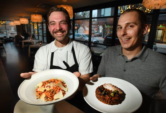 Chef de cuisine Matt Mayer with a carrot salad with walnut vinaigrette, parmesan and poached egg and chef Nick Janutol with a black rice with roasted tomato, sesame and nori in the dining room of Forest in Birmingham.