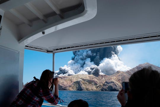 In this Dec. 9, 2019, photo provided by Michael Schade, tourists on a boat look at the eruption of the volcano on White Island, New Zealand.