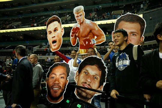 Fans hold cardboard heads of players from the Dallas Mavericks and Detroit Pistons prior to Thursday's game in Mexico City.