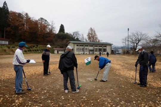 A group of seniors play gateball in a school yard Wednesday, Nov. 27, 2019, in Date, Fukushima prefecture, Japan.