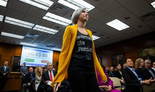 Amanda Thomashow, a survivor,  approaches the microphone to speak during the Michigan State Board of Trustees meeting on Friday.