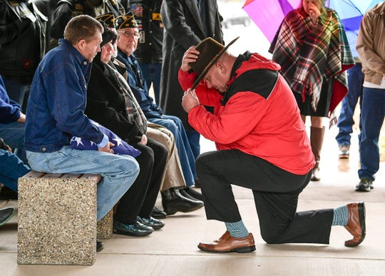 Jeff Fultz, Dolly Cooper Veterans Cemetery supervisor,  kneels in front of the family of United States Army veteran William D. Rowland, 64, homeless in the Pickens area, at Dolly Cooper Veterans Cemetery in Anderson Friday, December 13. Private Second Class Rowland was born 1955 in Pickens, enlisted in the United States Army in 1972 and later received a National Defense Service Medal as a rifle Sharpshooter.