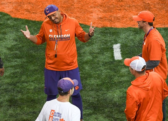 Clemson co-offensive coordinator Tony Elliott shrugs his shoulders talking with Clemson Head Coach Dabo Swinney, below, Clemson quarterbacks coach Brandon Streeter, lower right, and new wide receiver coach Tyler Grisham during practice at the Poe Indoor Facility in Clemson Friday, December 13, 2019. The Tigers are preparing for the College Football Playoffs semi-final game with Ohio State University played in Glendale, Arizona on December 28, 2019.