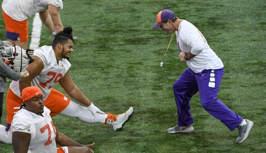 Clemson offensive lineman Jackson Carman (79) smiles as Clemson Head Coach Dabo Swinney shows a offensive lineman move during practice at the Poe Indoor Facility in Clemson Friday, December 13, 2019. The Tigers are preparing for the College Football Playoffs semi-final game with Ohio State University played in Glendale, Arizona on December 28, 2019.