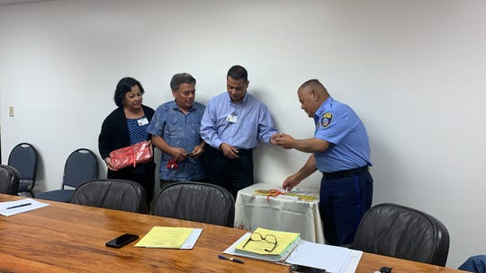 Guam Housing and Urban Renewal Authority Director Ray Topasna hands over keys to Guam Police Department Chief Steve Ignacio to the central precinct command in Sinajana during a GHURA board meeting on Dec. 13, 2019.