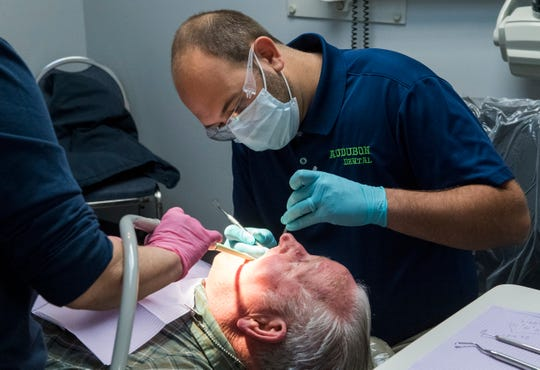Dr. Zack Gregory, right, works on patient James Yates, center during Audubon Dental Center's annual Christmas Care Day in Henderson, Ky., Friday morning, Dec. 13, 2019. The first 50 people were treated to free dental care, a service Audubon Dental Center has been providing for more than 20 years.