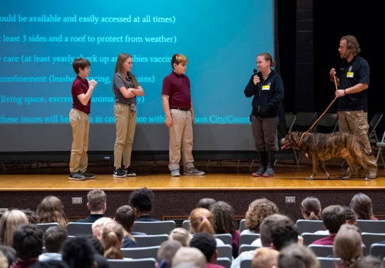 Middle-schoolers learn how to greet a dog with the help of Animal Control officers Alyssa Davis, second right, Neal Overfield, right, and Fatboy, a rescue dog Overfield adopted, during the Building Animal Responsibility and Knowledge (B.A.R.K.) program presented by the Henderson Humane Society and Animal Control at South Middle School Wednesday afternoon. The kids were taught the basics of dog care which included feeding, vaccinations and shelter.at South Middle School Wednesday afternoon.