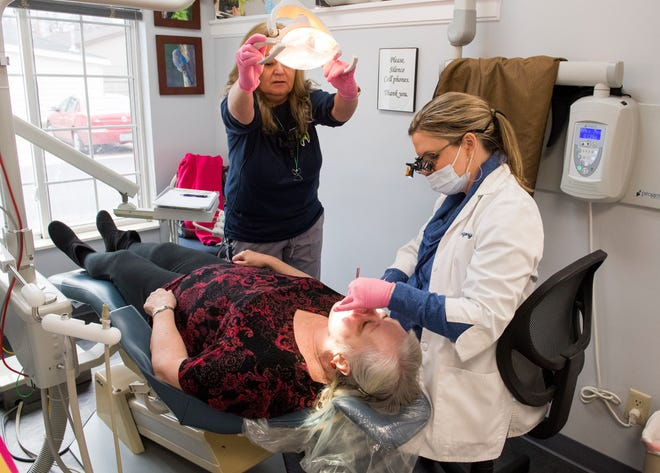 Assistant Lisa Thomas, center, adjust the overhead light for Dr. Chelsey Gregory, right, while she inspects the teeth of Terry Coker, center, during Audubon Dental Center's annual Christmas Care Day in Henderson, Ky., Friday morning, Dec. 13, 2019. The first 50 people were treated to free dental care, a service Audubon Dental Center has been providing for more than 20 years.