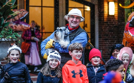 Governor Eric Holcomb holds the First Dog, Henry Holcomb, for trick or treaters to pet while dressed in a Jurassic Park theme during a snowy Halloween at the Indiana Governors Mansion on Wednesday, Oct. 31, 2019. The Gov., First Lady, and staff handed out candy and free passes the Indiana State Parks.