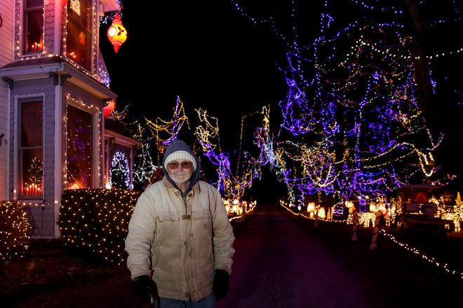 Calvin Cottrell poses for a photo as thousands of lights are displayed behind him around his home, Thursday, Dec. 12, 2019 in Rossville.