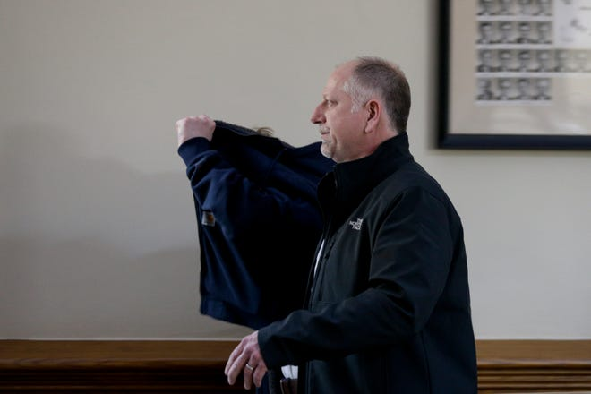 John D. Vanderwielen, back, uses his coat to conceal himself from the camera as he walks out of Tippecanoe County Courthouse Superior Court 2 with his father, Douglas Vanderwielen, Friday, Dec. 13, 2019 in Lafayette. John D. Vanderwielen is accused of aggravated battery with risk on life, domestic battery with a deadly weapon, battery with a deadly weapon, domestic battery, battery resulting in bodily injury, criminal recklessness with a deadly weapon, resisting law enforcement and possession of paraphernalia after allegedly taking three hits of acid before attacking his parents.