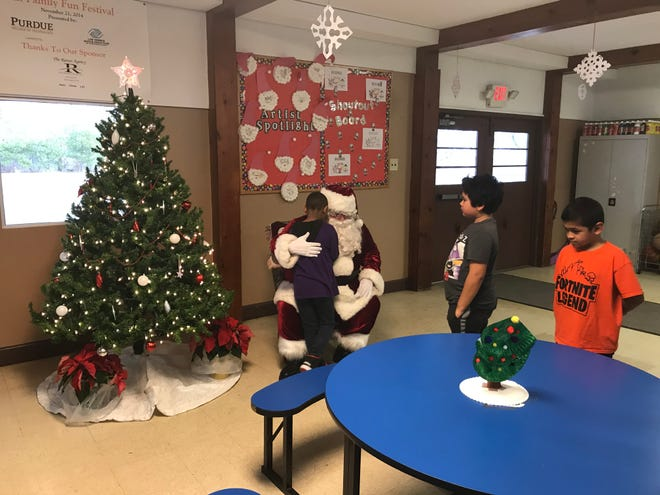 Santa Claus listens to what children at the Beck Lane Boys and Girls Club want for Christmas during a celebration of the organization's twentieth anniversary at the location.