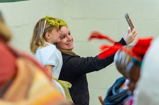 A mom snaps a selfie with her child at a pre-K performance of Christmas carols at Green T. Lindon Elementary in Youngsville Friday, Dec. 13, 2019.