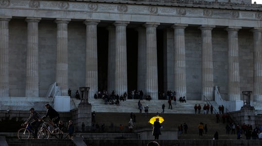 A yellow umbrella catches a ray of sunshine in front of the Lincoln Memorial in Washington D.C.