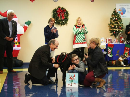 Kosair Charities President Keith Inman presented an assistive technology gift to 10-year-old Braydon Brotzge during the enTECH Day of Celebration at Spalding University on Wednesday, Dec. 11. Brayon was there with his mother, Terra, and service dog, Slim.