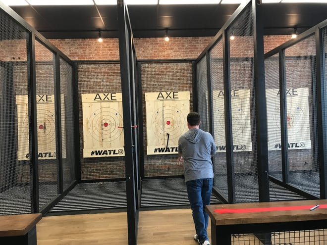 Erik Flick, who with his wife Emily, owns the new Axe Social Lounge at 123 N. Diamond St., demonstrated the art of throwing an axe at the new business Friday.