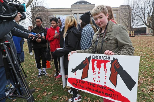 Shorewood High School sophomore Madeline O'Connell, 16, holds her handmade sign as students share their thoughts with media after they walked out of school Friday.