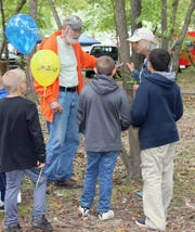 Ed Metcalf of Lakeview and Barb Bremer of Mountain Home show children how to identify trees from their leaves and bark at the Celebrate Lakeview event.