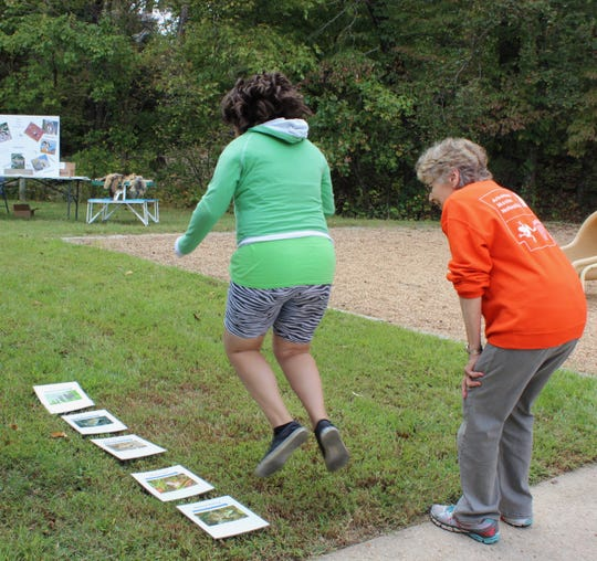 With encouragement of Suzanne Harrison of Mountain View, children compare how far they can jump to the leaping distances of native Arkansas frogs during a spring nature celebration.