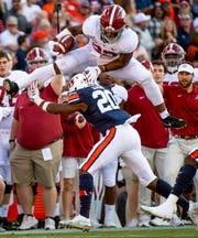 Alabama running back Najee Harris (22) hurdles Auburn defensive back Jeremiah Dinson (20) in first half action in the Iron Bowl at Jordan-Hare Stadium in Auburn, Ala., on Saturday, November 30, 2019.