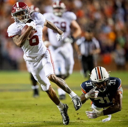 Alabama wide receiver DeVonta Smith (6) shakes the tackle of Auburn linebacker Chandler Wooten (31) in second half action in the Iron Bowl at Jordan-Hare Stadium in Auburn, Ala., on Saturday, November 30, 2019.