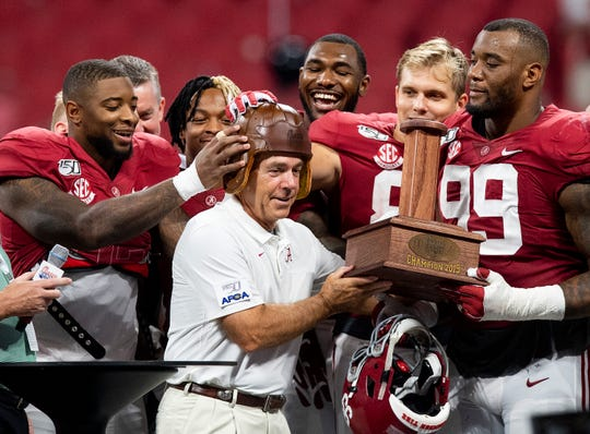 Players place the Old Leather Football Helmet Alabama head coach Nick Saban after defeating Duke in the Chick-fil-A Kickoff Game at Mercedes Benz Stadium in Atlanta, Ga., on Saturday August 31, 2019.