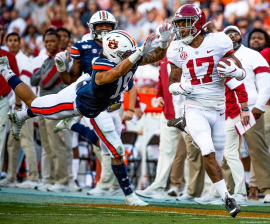 Alabama wide receiver Jaylen Waddle (17) gets by Auburn wide receiver Matthew Hill (19) as Waddle scores a touchdown on a kick return in first half action in the Iron Bowl at Jordan-Hare Stadium in Auburn, Ala., on Saturday, November 30, 2019.