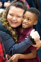 Learius McDougal, right, is embraced by Jennie Alexander during the Cold Feet, Warm Shoes event at Park Avenue Elementary School on Dec. 13, 2019. Genesco volunteers fit children with socks, a new pair of shoes and a sweatshirt.