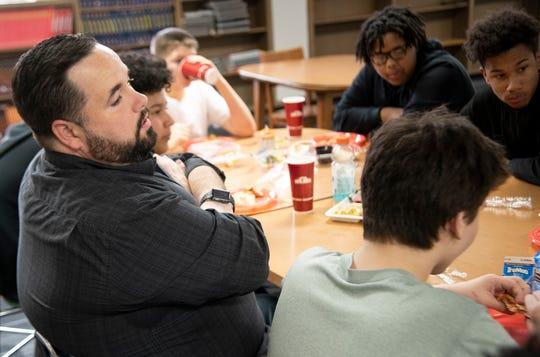 Daniel Burnell chats with eighth graders as he volunteers with the mentor lunch program at Wright Middle School on Thursday, Dec. 12, 2019.