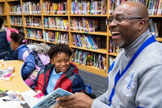 Reggie Grimes Sr. reads with Michael Mason (left) during Fatherhood Friday at Buena Vista Elementary Friday, Dec. 13, 2019, in Nashville, Tenn.
