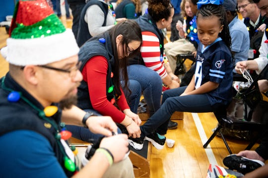 D'Shawndra Cotten, 7, looks down at shoes during the Cold Feet, Warm Shoes event at Park Avenue Elementary School Friday. Genesco volunteers fitted children with socks, a new pair of FILA shoes and sweatshirt.