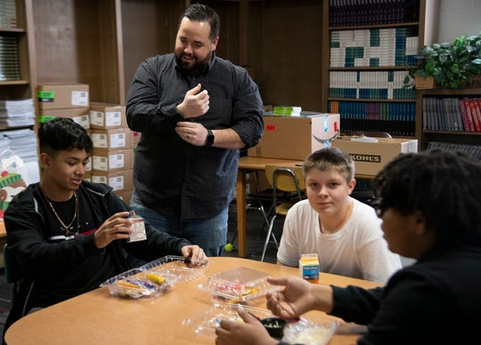 Daniel Burnell chats with eighth graders Alex Lara, Daven Johnson and D'Avante Covington as he volunteers for the mentor lunch program at Wright Middle School on Dec. 12, 2019.