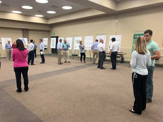 Attendees of the M-CORES community open house in Naples view displays and speak with FDOT officials on Thursday, Dec. 12.