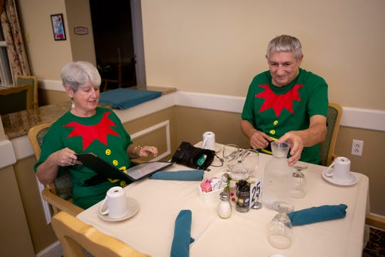 """Judy Albero, left, and Frank Albero, right, sit down for lunch in the dining room at Brookdale Bonita Springs on Friday, December 13, 2019. The Alberos, who lost their home in a fire in early September, say they often wear matching festive outfits, much to the amusement of their new neighbors. """"The people here love it,"""" Frank said."""