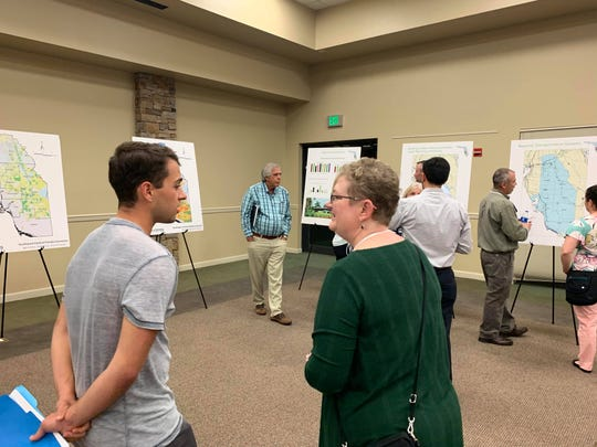 Attendees of the open house discuss the pros and cons of the M-CORES project in Naples on Thursday, Dec. 12.