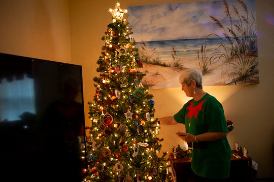 """Judy Albero looks at the ornaments on her Christmas tree at home at Brookdale Bonita Springs on Friday, December 13, 2019. The tree and all of its ornaments were some of the few items in the Alberos' home that were untouched by the fire, and Judy calls it their """"miracle tree."""""""
