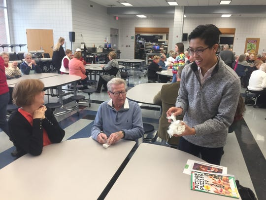 GHS junior Stephen Chang distributes utensils at the Dec. 13 event that brought more than 200 senior citizens to the school for a meal and music.
