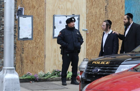 A police officer stands in front of a boarded up Kosher Market on December 13, 2019 following Tuesday's shootout in Jersey City that left six people dead.