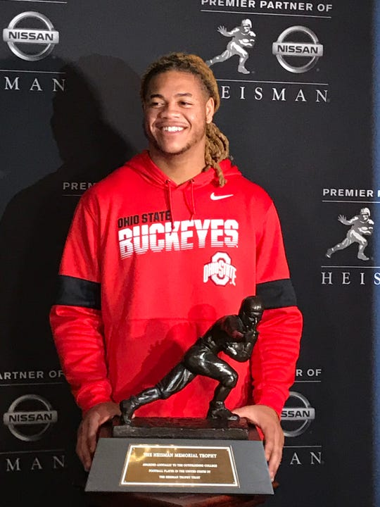Ohio State star defensive end Chase Young poses with the Heisman Trophy. He is a finalist for college football's most prestigious award.