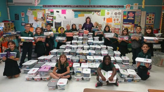 Second grade LCCS students stand behind the boxes they prepared to donate to children across the world.