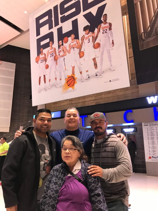 Robert Rivera, 34, of Phoenix, far right, with his cousins, Abraham Holguin, 58, center, Armando Lozano, 43, far left, and Sylvia Holguin, 61, at the Suns game on Monday night against the Minnesota Timberwolves. The four cousins are Mexican-Americans and die-hard Suns fans. The Suns are trying to do more to reach out to Latinos in Arizona.