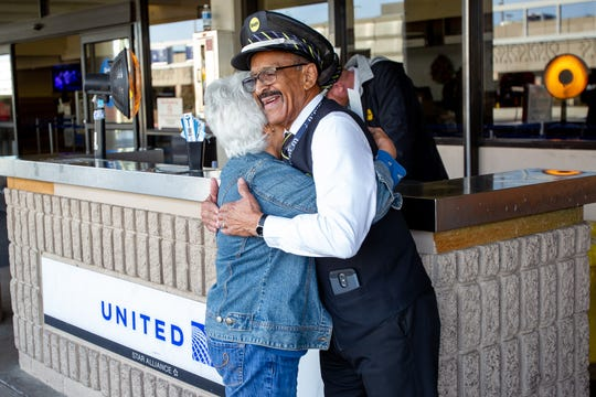 Lou Davis hugs a passenger after helping her with her luggage and telling her which gate to go to on Dec. 3, 2019.