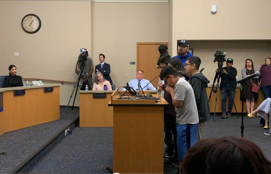 A family with children at Emerson Elementary speak at the Phoenix Elementary School District school board meeting, opposing the proposed closures of three schools on Thursday, Dec. 12, 2019.