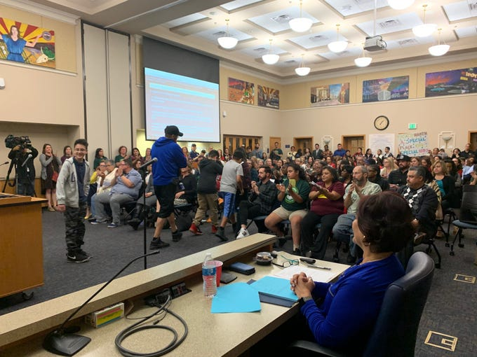 A family with children at Emerson Elementary leave the podium after speaking at the Phoenix Elementary School District school board meeting, opposing the proposed closures of three schools on Thursday, Dec. 12, 2019.
